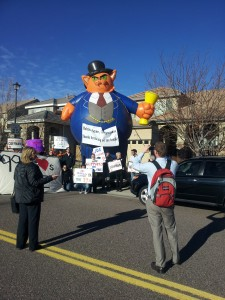 "Reporter photographing inflatable ""Fat Cat,"" erected by activists to show Rep. Mike Coffman's ties to wealthier Americans"